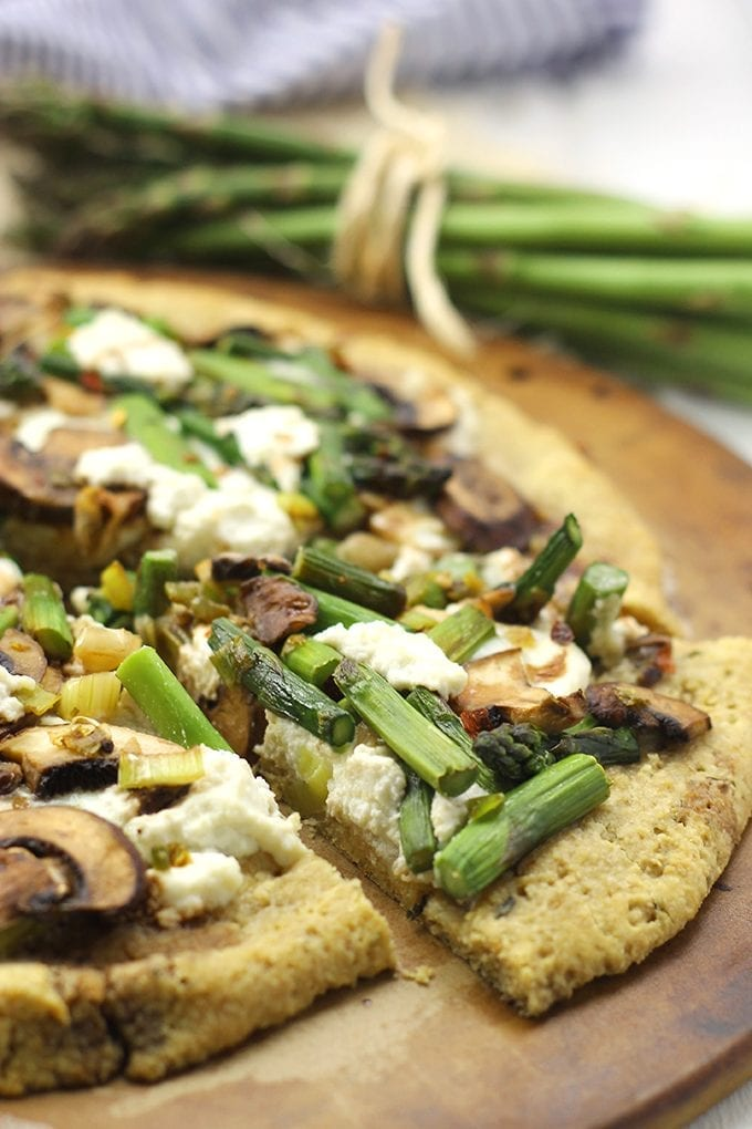 Pizza just got a healthy makeover with this Mushroom Asparagus and Ricotta Pizza! Topped with fresh veggies on a grain-free, almond meal and cauliflower crust, this recipe will make you never want to order in a delivery pizza again.