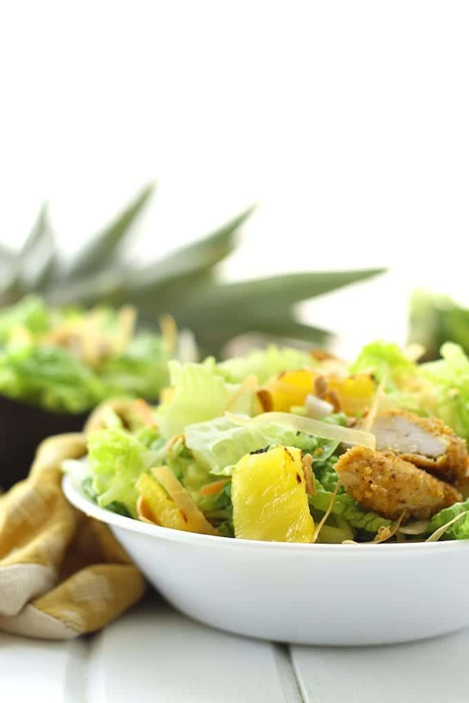 A nutritious and gluten-free salad recipe made with veggies, cashew crusted chicken bites, toasted noodles and pineapple. This Crunchy Asian Chicken Salad is the ultimate asian-inspired salad recipe for a healthy weeknight dinner or lunch on-the-go.