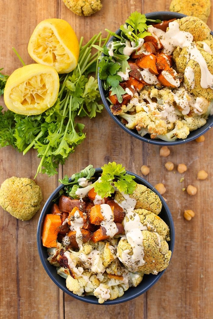 East meets West with these Baked Falafel Buddha Bowls! Made with quinoa, roasted vegetables, greens and of course, baked falafel this vegan and gluten-free recipe makes a complete meal in one.