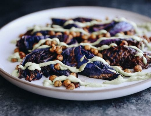 A horizontal picture of roasted cabbage steaks with crispy chickpeas and a cashew-based creamy herb sauce