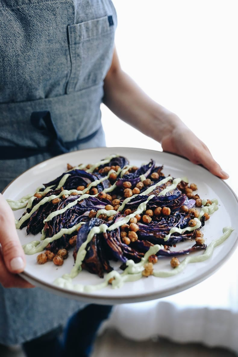 A picture of a woman holding a place of roasted cabbage with chickpeas on top and drizzled with a green herb sauce