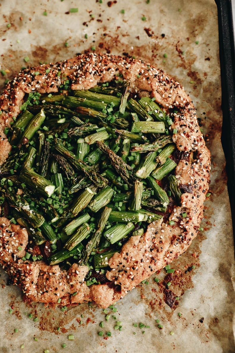 Get a taste of summer with this savory galette recipe with goat cheese, asparagus and caramelized onions. Made with a spelt crust and savory veggie goat cheese base for a delicious meal.